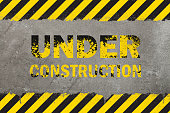 Concrete weathered wall background with yellow and black painted grunge hazard sign stripes and under construction message