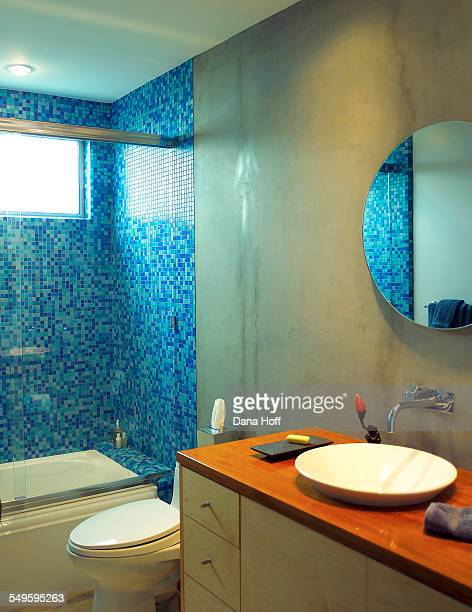 Concrete bathroom with blue tiles in the shower