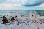 Seascape with the sea surf breaking on the concrete conical boulders