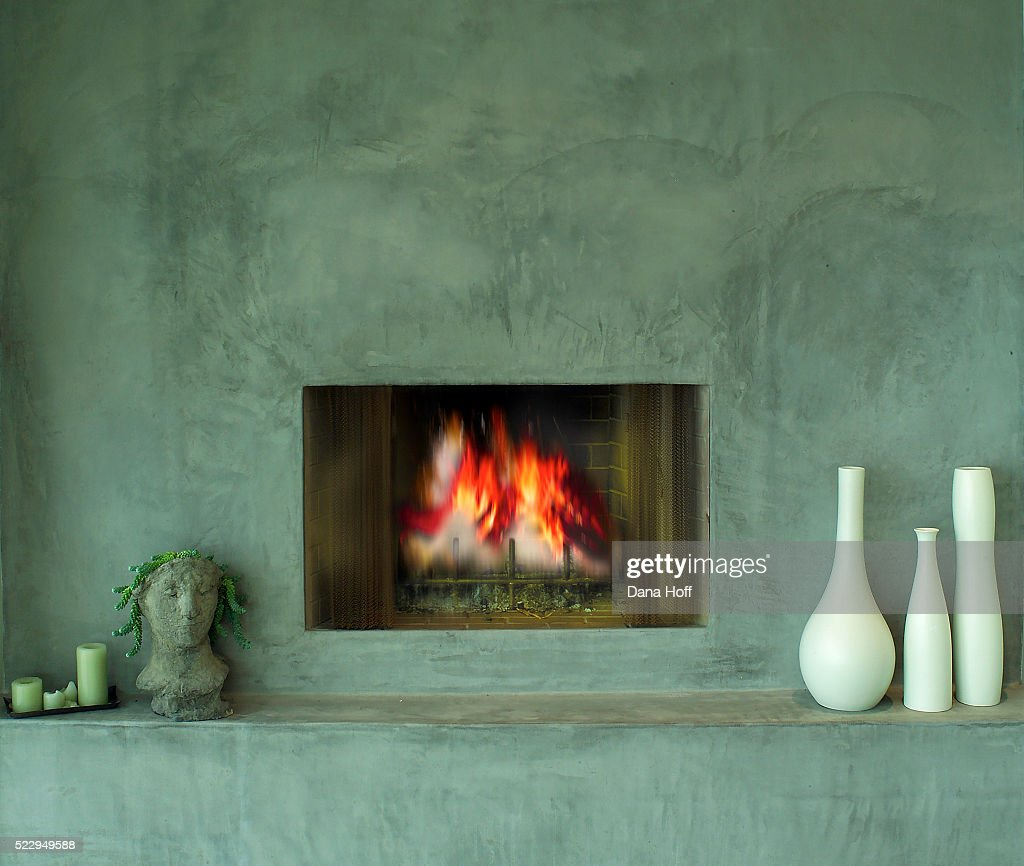 concrete fireplace with white vases on the hearth stock photo