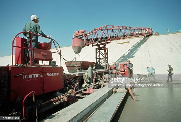 Concrete is poured from a mixer on the edge of the California Aqueduct to a concrete laying machine during the construction phase California