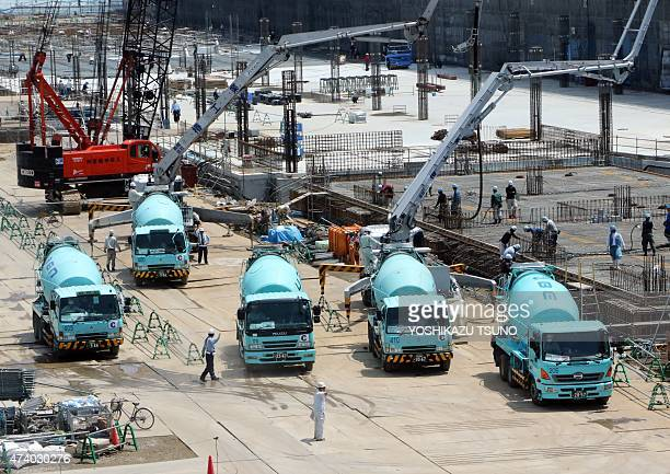 Concrete mixer trucks queue up at a large building in Tokyo on May 20 2015 Japan's economy grew more than expected in the first three months of the...
