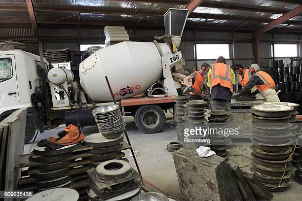A concrete mixer unloads freshly mixed concrete onto a table where workers shovel it into molds at the warehouse of Gully Concrete supplies in...