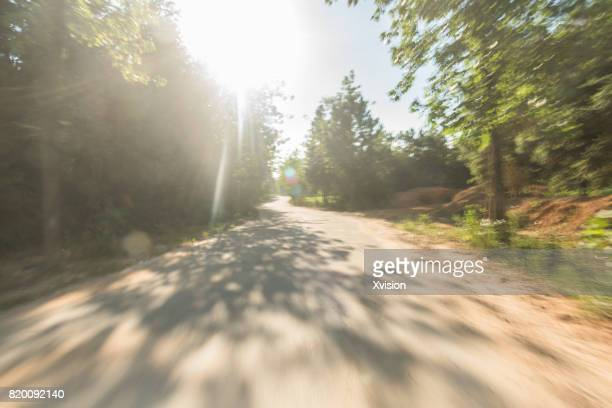 Concrete road under blue sky with clouds in motion blur with plants in sides