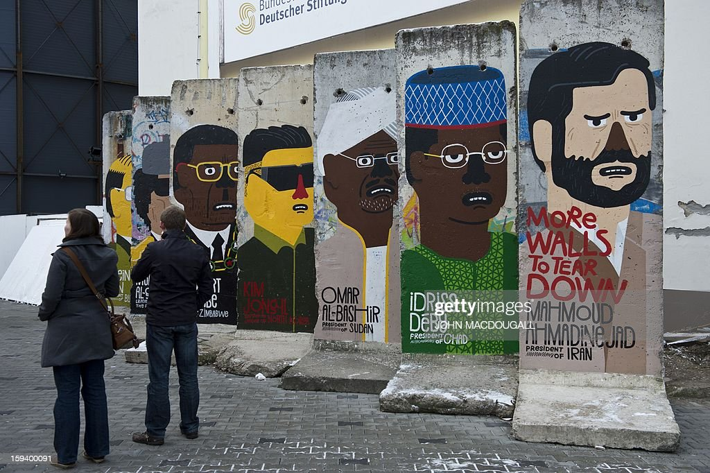 Concrete slabs from the former Berlin wall are decorated with likenesses of (from R) Iranian President Mahmoud Ahmadinejad, Chad's President Idriss Deby, Sudan's President Omar Al-Bashir, former North Korean leader Kim Jong-il, and Zimbabwe's President Robert Mugabe, by French artist Guillaume Kashima, near the city's Checkpoint Charlie area, on January 13, 2013.
