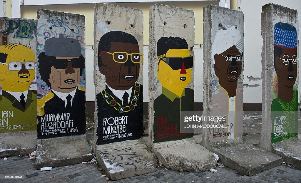 Concrete slabs from the former Berlin wall are decorated with likenesses of (from R) Chad's President Idriss Deby, Sudan's President Omar Al-Bashir, former North Korean leader Kim Jong-il, Zimbabwe's President Robert Mugabe, and Burma's President Thein Sein, by French artist Guillaume Kashima, near the city's Checkpoint Charlie area in Berlin on January 13, 2013.