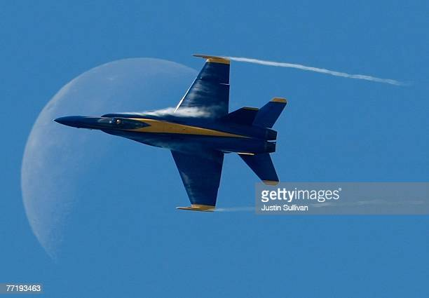 Condensation comes off the wings of a US Navy Blue Angels F/A18 Hornet as it passes in front of the moon during a practice session for San Francisco...