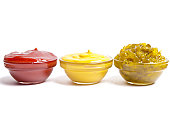 Small bowls of ketchup, mustard and pickle relish.
