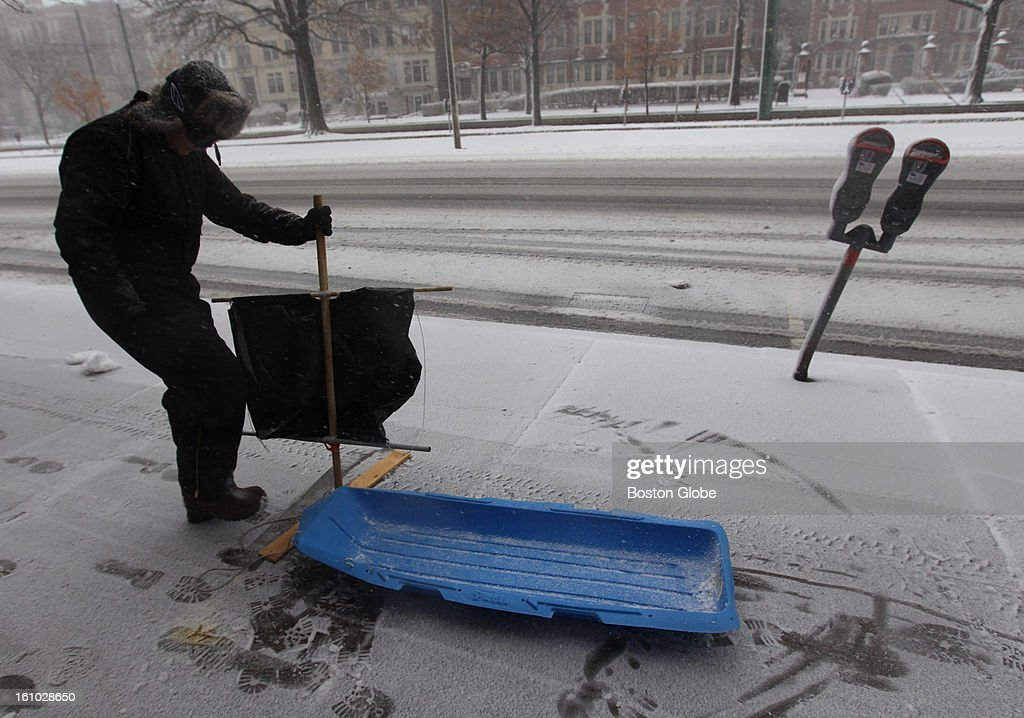 Peter Strounine of Brookline uses a trash bag and a sled to test out his method of transportation on Beacon Street in Brookline.