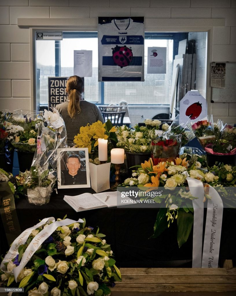 A condolence book and flowers are displayed in memory of linesman Richard Nieuwenhuizen at the clubhouse of Dutch football club SC Buitenboys in Almere, on December 9, 2012. Nieuwenhuizen collapsed and fell into a coma after he was attacked by three teenagers at the end of a junior club football match on December 2, 2012. People will gather this afternoon for a silent march in memory of Nieuwenhuizen. AFP PHOTO/ANP/ KOEN VAN WEEL netherlands out