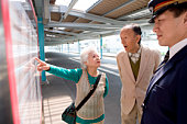 Conductor and senior couple looking at arrival departure board at platform