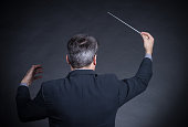 Conductor with back to camera gesturing with baton