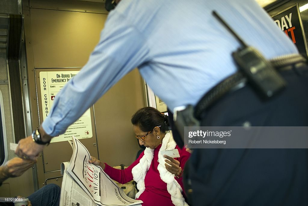 A conductor checks tickets on a Metro North train on November 23, 2012 in New Haven, Connecticut before heading to New York's Grand Central Station.