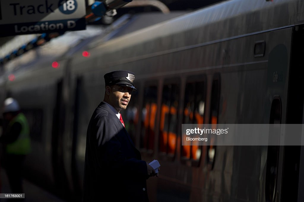 Conductor Claude Robinson stands on the Amtrak Acela platform at Union Station in Washington, D.C., U.S., on Friday, Feb. 15, 2013. Amtrak, the U.S. long-distance passenger railroad and federally subsidized since its beginning 41 years ago, last month reported its lowest operating loss in nearly four decades, announcing the passenger rail company had reduced its total operating loss by 19 percent compared to the previous year. Photographer: Andrew Harrer/Bloomberg via Getty Images