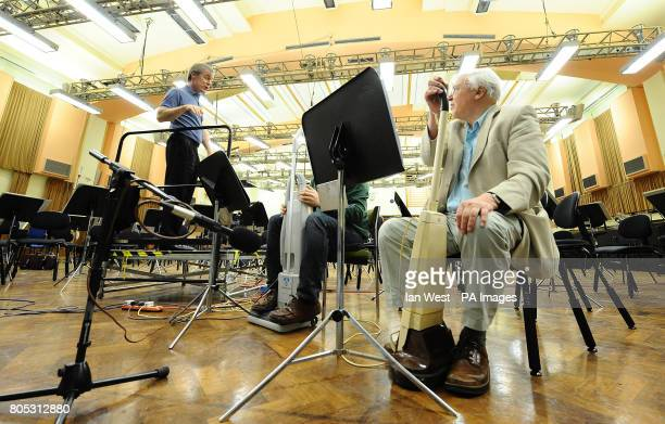 Conductor David Robertson leads Sir David Attenborough with a floor polisher during a rehearsal for Sir Malcolm Arnold's 'A Grand Grand Overture'...