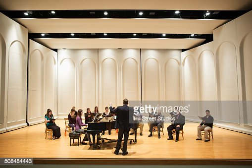 Conductor directing choir on stage