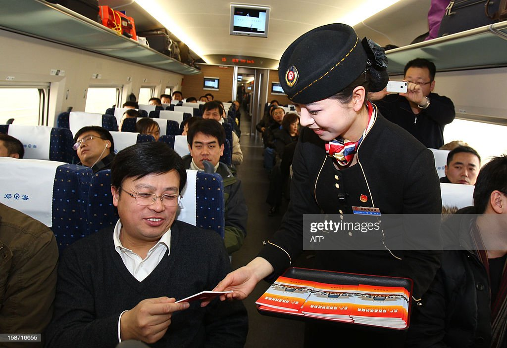 A conductor gives out a booklet to a passenger on the high speed train that runs on the new 2,298-kilometre (1,425-mile) line between Beijing and Guangzhou at a train station in Zhengzhou, central China's Henan province on December 26, 2012. China started service on December 26 on the world's longest high-speed rail route, the latest milestone in the country's rapid and -- sometimes troubled -- super fast rail network. The opening of this new line means passengers will be whisked from the capital to the southern commercial hub in just eight hours, compared with the 22 hours previously required. CHINA OUT AFP PHOTO