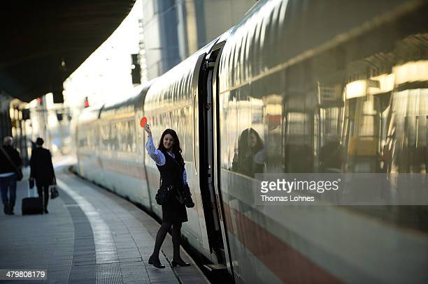 A conductor gives the sign for the departure of an ICE train at the central railway station on March 20 2014 in Frankfurt Germany Deutsche Bahn...