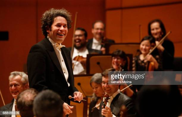 SEQUENCE Conductor Gustavo Dudamel laughs with members of the LA Philharmonic as a lone concertgoer hoots after the first movement of Schubert's...