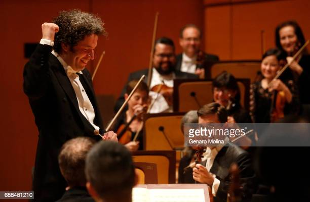 SEQUENCE Conductor Gustavo Dudamel raises a fist acknowledging a lone concertgoer's hoot after the first movement of Schubert's Symphony No 4...