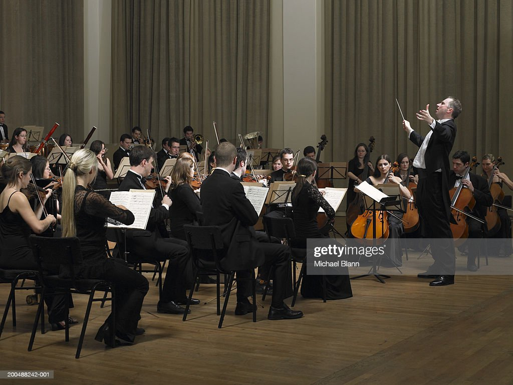 Conductor leading orchestra : Stockfoto