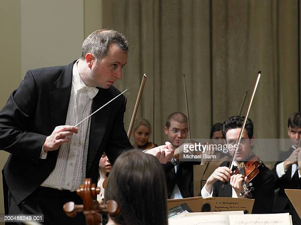 Conductor leading violin section of orchestra