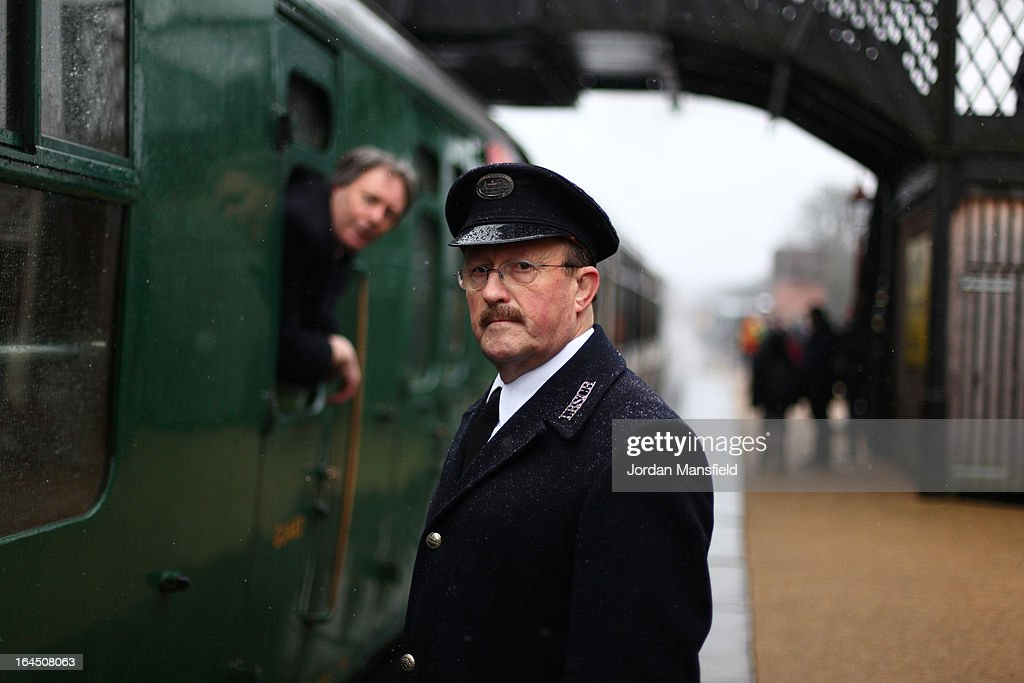 A conductor looks on as a locomotive arrives at Sheffield Park Station on March 23, 2013 in Fletching, England. The Bluebell Railway ran its first steam train this weekend on the reclaimed line from Kingscote to East Grinstead after volunteers from the Bluebell Society worked to reopen the line after its closure on March 17, 1958. 50 years on from Dr. Richard Beeching's report signaling the widespread closure of rural rail routes across the UK, Britain's railways are in great demand with old lines reopening and pressure on to restore rural lines that were closed.