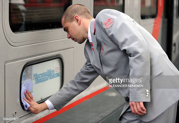 A conductor of a new luxury train running between Moscow and Nice cleans a plaque at Moscow's Belorussky station on September 23 2010 A train began...