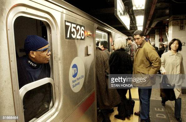 A conductor on the number 6 line of the New York City subway watches passengers board the train 13 December at Grand Central Terminal in New York The...