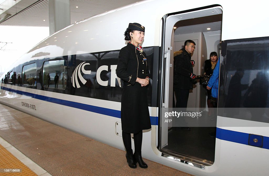 A conductor stands beside the high speed train of the new 2,298-kilometre (1,425-mile) line between Beijing and Guangzhou at a train station in Zhengzhou, central China's Henan province on December 26, 2012. China started service on December 26 on the world's longest high-speed rail route, the latest milestone in the country's rapid and -- sometimes troubled -- super fast rail network. The opening of this new line means passengers will be whisked from the capital to the southern commercial hub in just eight hours, compared with the 22 hours previously required. CHINA OUT AFP PHOTO