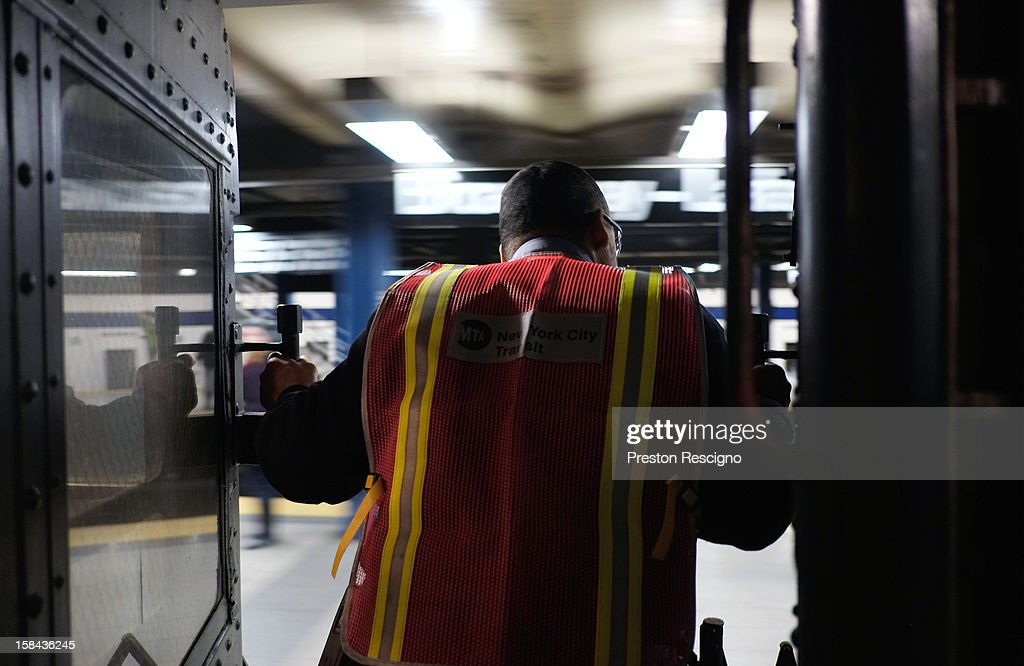 A conductor stands between cars as a vintage New York City subway leaves the station on December 16, 2012 in New York City. The New York Metropolitan Transportation Authority (MTA) runs vintage subway trains from the 1930's-1970's each Sunday along the M train route from Manhattan to Queens through the first of the year.