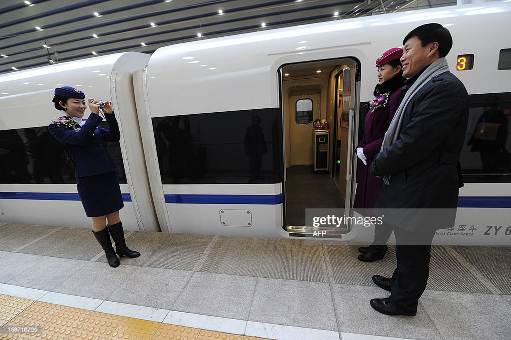 A conductor takes a photo of a passenger beside the high speed train of the new 2,298-kilometre (1,425-mile) line between Beijing and Guangzhou as it waits to start off in Beijing on December 26, 2012. China started service on December 26 on the world's longest high-speed rail route, the latest milestone in the country's rapid and -- sometimes troubled -- super fast rail network. The opening of this new line means passengers will be whisked from the capital to the southern commercial hub in just eight hours, compared with the 22 hours previously required. CHINA