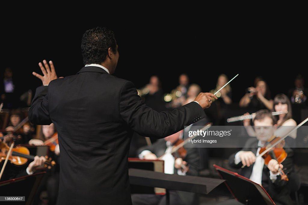 Conductor waving baton over orchestra