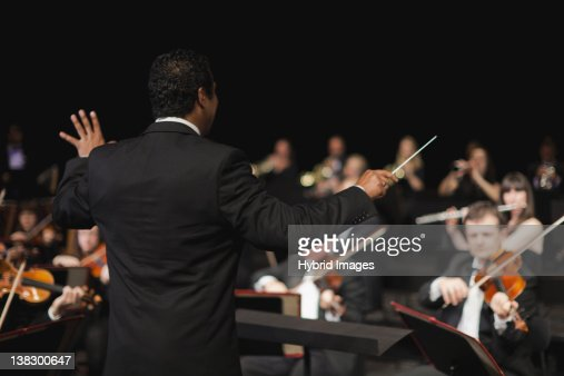 Conductor waving baton over orchestra