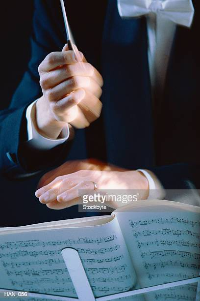 Conductor's hands waving baton over music stand