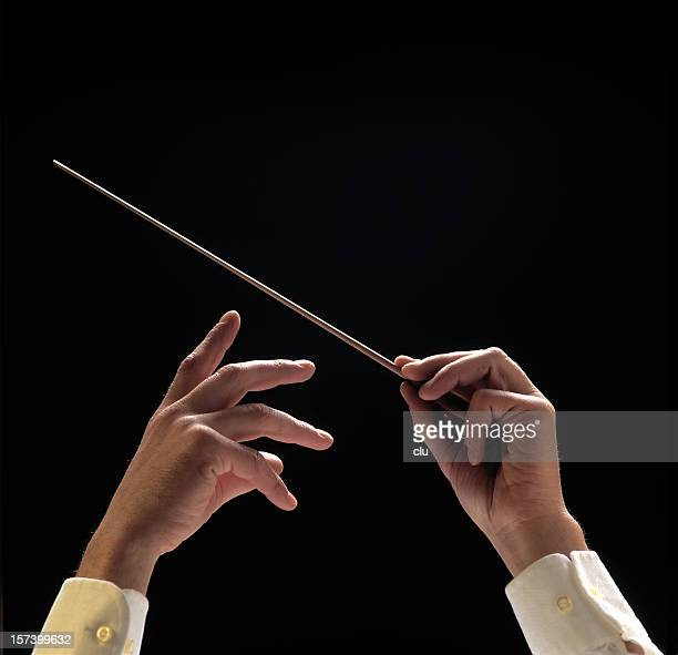 Conductors hands with baton on black background