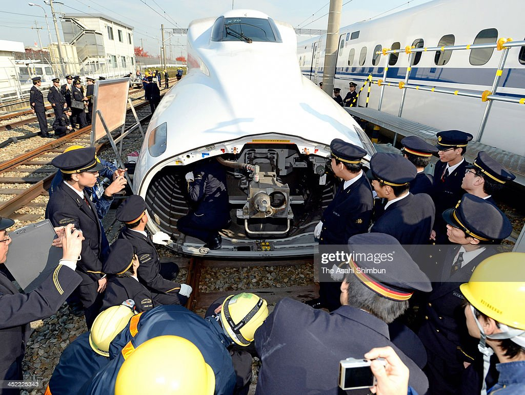 Conductors prepare to pull out a traction coupler from the first car of a Shinkansen bullet train on November 27, 2013 in Settsu, Osaka, Japan. In preparation for the ever-present threat of a powerful temblor disrupting Shinkansen service, more than 1,000 people participated in an emergency drill conducted by Central Japan Railway Co. (JR Tokai) at its Torikai base for bullet trains.