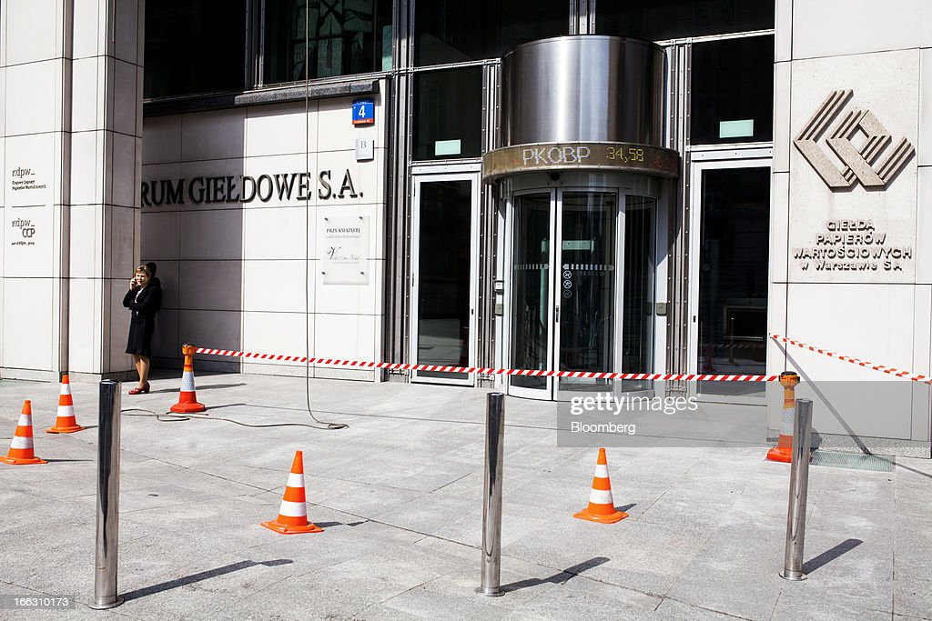 Cones and tape cordon an area outside the entrance to the Warsaw Stock Exchange during exterior cleaning work in Warsaw, Poland, on Thursday, April 11, 2013. Poland's central bank kept interest rates unchanged at a record-low 3.25 percent yesterday. Photographer: Bartek Sadowski/Bloomerg