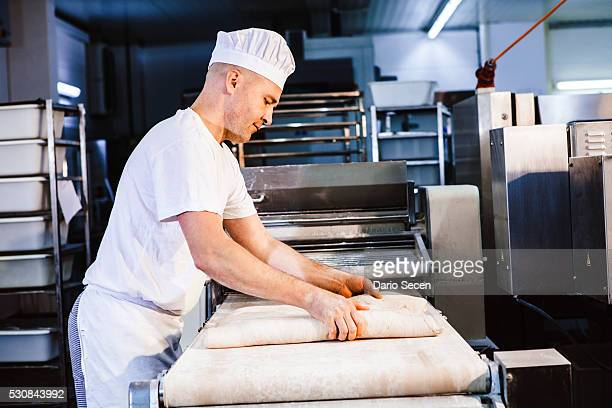 Confectioner kneading pastry dough in bakery