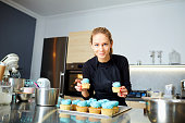 Confectioner pastry woman holding a tray of cupcakes in the kitchen.
