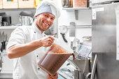 Handsome confectioner in chef uniform producing ice cream with ice cream machine