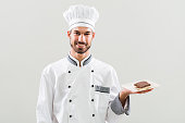 Confectioner is showing slices of cake on gray background.