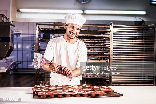 Confectioner working with icing bag in bakery