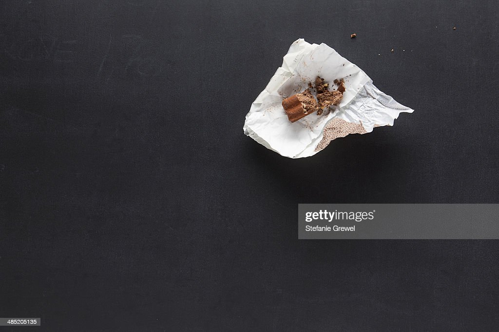 Confectionery in paper wrapper on blackboard