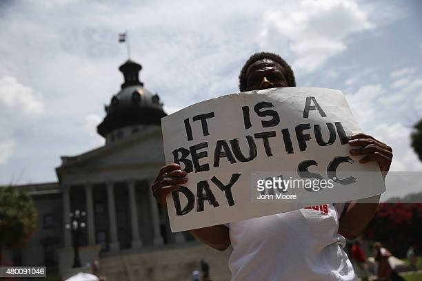Confederate flag protester holds a sign before a ceremony where Governor Nikki Haley was to sign a bill removing the Confederate flag from outside...