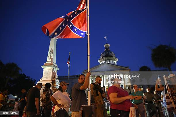 Confederate flag supporters stand outside the as 'Stars and Bars' flies in front of the South Carolina statehouse on its last evening on July 9 2015...