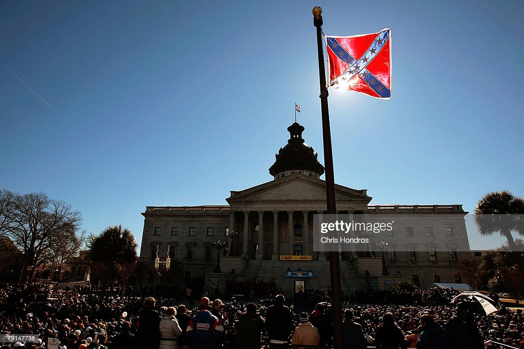 Confederate flag that's part of a Civil War memorial on the grounds of the South Carolina State House flies over a Martin Luther King Day rally...