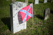 Confederate flags stand next to the headstone's of Confederate States of America soldiers at the Magnolia Cemetery in Charleston South Carolina June...