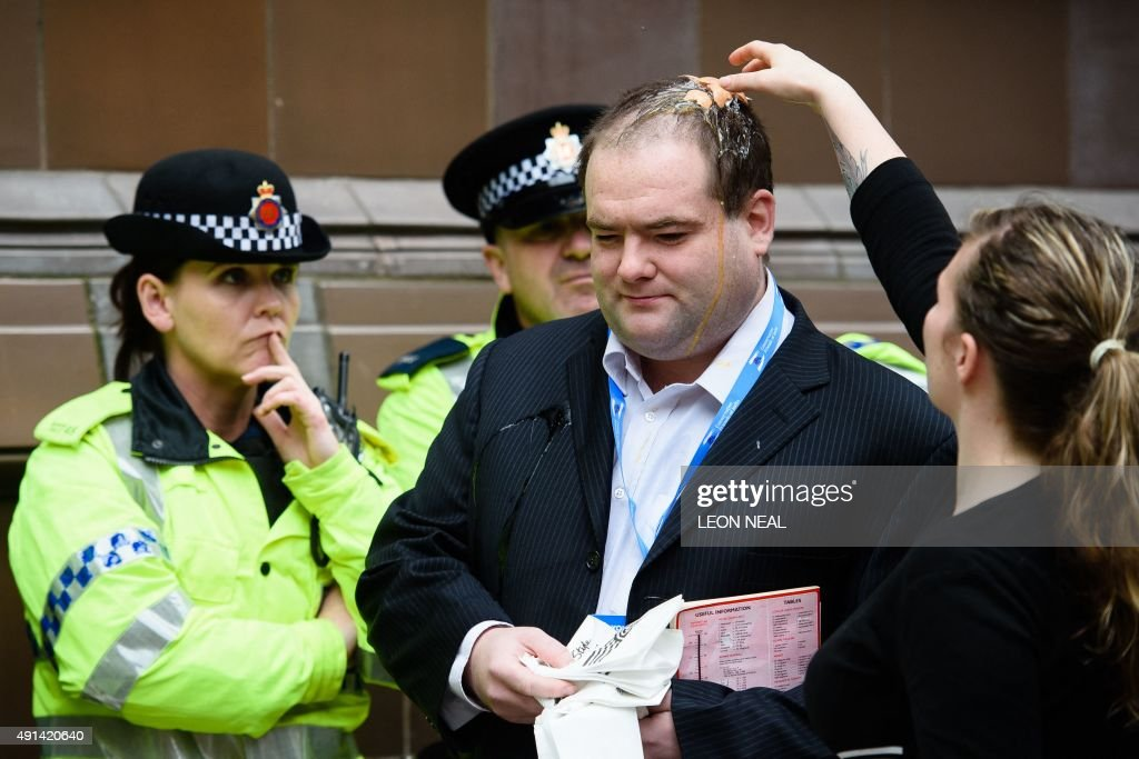A conference attendee talks to police officers after being hit by an egg thrown by protestors on the second day of the annual Conservative party...