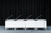 Monochrome picture of conference stand table with microphones in a meeting room